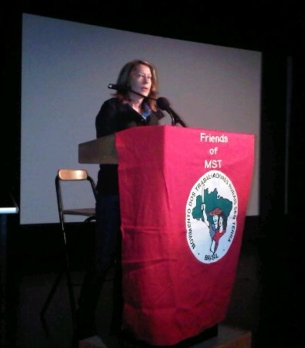 Balliger introduces International Day of Peasant Struggle at SFAI, 2011, at podium with banner of Friends of MST