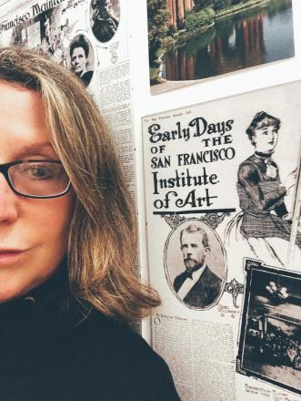 Balliger in front of old poster with text: Early Days of the San Francisco Institute of Art