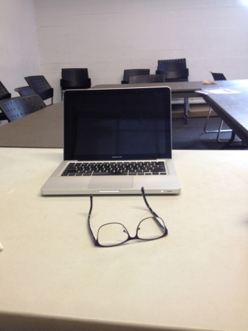 Classroom desk with computer and eye glasses